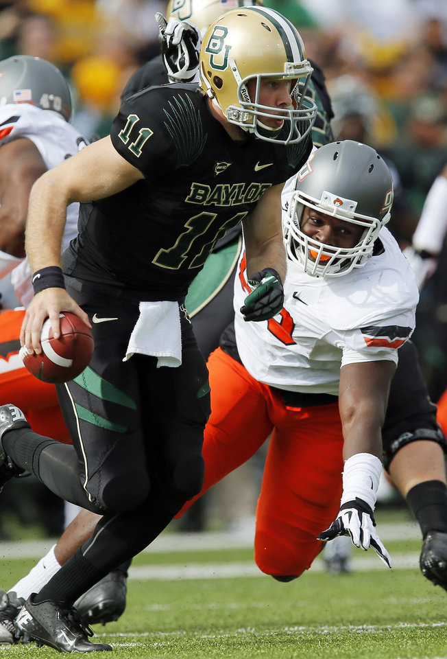 Photo - Baylor's Nick Florence (11) scrambles away from Oklahoma State's Nigel Nicholas (89) during a college football game between the Oklahoma State University Cowboys (OSU) and the Baylor University Bears at Floyd Casey Stadium in Waco, Texas, Saturday, Dec. 1, 2012. Photo by Nate Billings, The Oklahoman