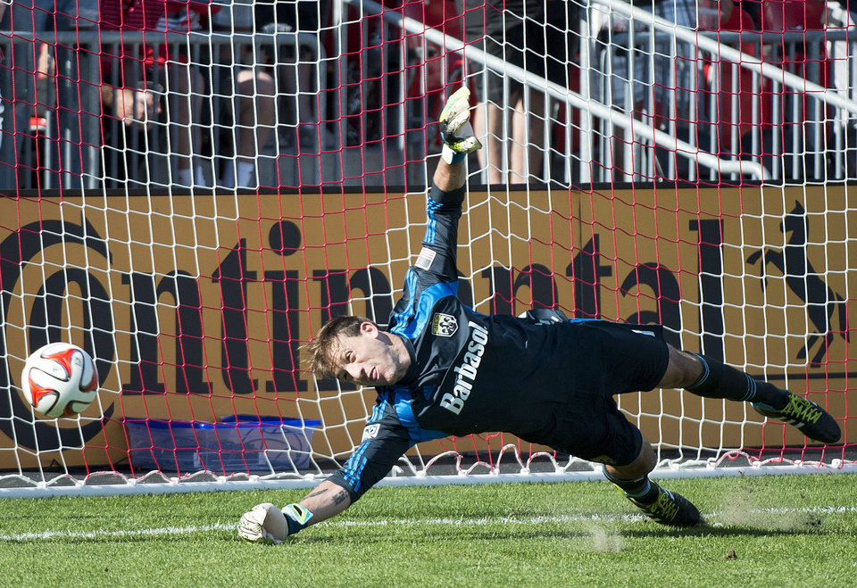 Photo - Columbus Crew goalkeeper Steve Clark is unable to make a save on a penalty kick by Toronto FC forward Jermain Defoe during the first half of a MLS soccer game in Toronto on Saturday May 31, 2014. (AP Photo/The Canadian Press, Nathan Denette)