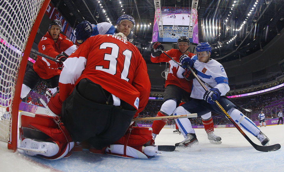 Photo - Canada goaltender Carey Price smothers the rebound as defenseman Jay Bouwmeester battles for position against period Finland forward Jori Lehtera in the first period of a men's ice hockey game at the 2014 Winter Olympics, Sunday, Feb. 16, 2014, in Sochi, Russia. Canada won 2-1 in overtime. (AP Photo/Mark Blinch, Pool)