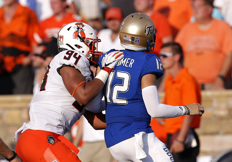 Photo - Oklahoma State's Trace Ford (94) pressures Tulsa's Seth Boomer (12) during a college football game between the Oklahoma State University Cowboys (OSU) and the University of Tulsa Golden Hurricane (TU) at H.A. Chapman Stadium in Tulsa, Okla., Saturday, Sept. 14, 2019. [Sarah Phipps/The Oklahoman]