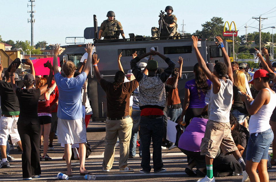 Photo - Protesters raise their hands in front of police atop an armored vehicle in Ferguson, Mo. on Wednesday, Aug. 13, 2014. On Saturday, Aug. 9, 2014, a police officer fatally shot Michael Brown, an unarmed black teenager, in the St. Louis suburb. (AP Photo/St. Louis Post-Dispatch, J.B. Forbes)