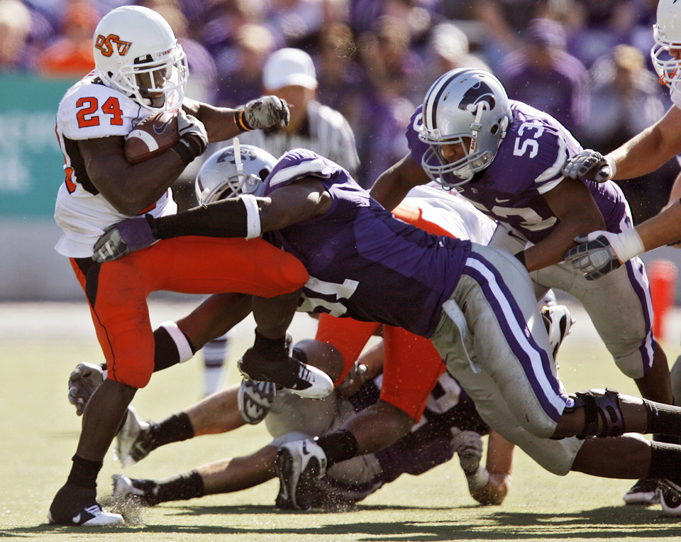 Photo - Oklahoma State's Kendall Hunter (24) tries to escape the Kansas State defense during the second half of the college football game between the Oklahoma State University Cowboys (OSU) and the Kansas State University Wildcats (KSU) on Saturday, Oct. 30, 2010, in Manhattan, Kan.   Photo by Chris Landsberger, The Oklahoman