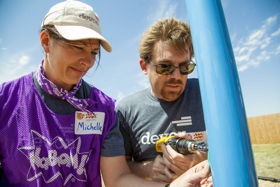 Photo -  Devon employees Michelle Jarret and Graham Gerner help assemble equipment at the Youth & Family Services playground project on Saturday in El Reno. PHOTO PROVIDED BY DEVON ENERGY