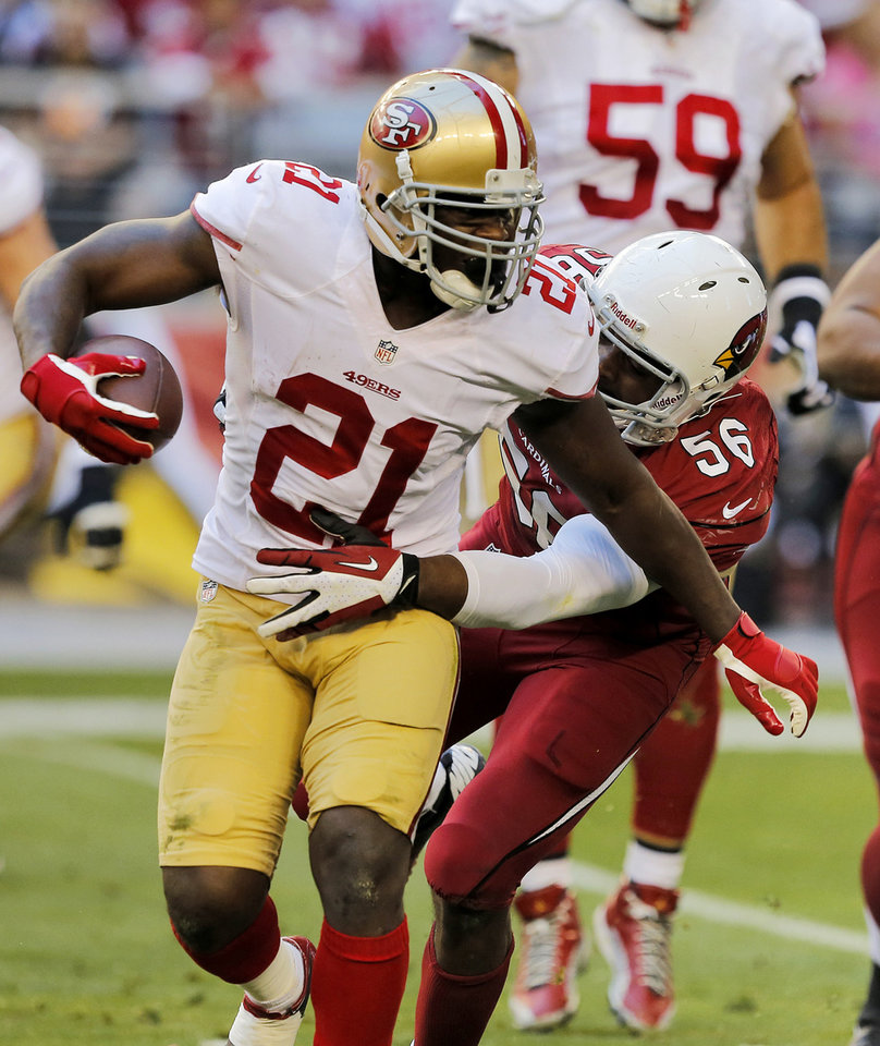 Photo - San Francisco 49ers running back Frank Gore (21) is tackled by Arizona Cardinals inside linebacker Karlos Dansby (56) during the first half of an NFL football game, Sunday, Dec. 29, 2013, in Glendale, Ariz.  (AP Photo/Rick Scuteri)