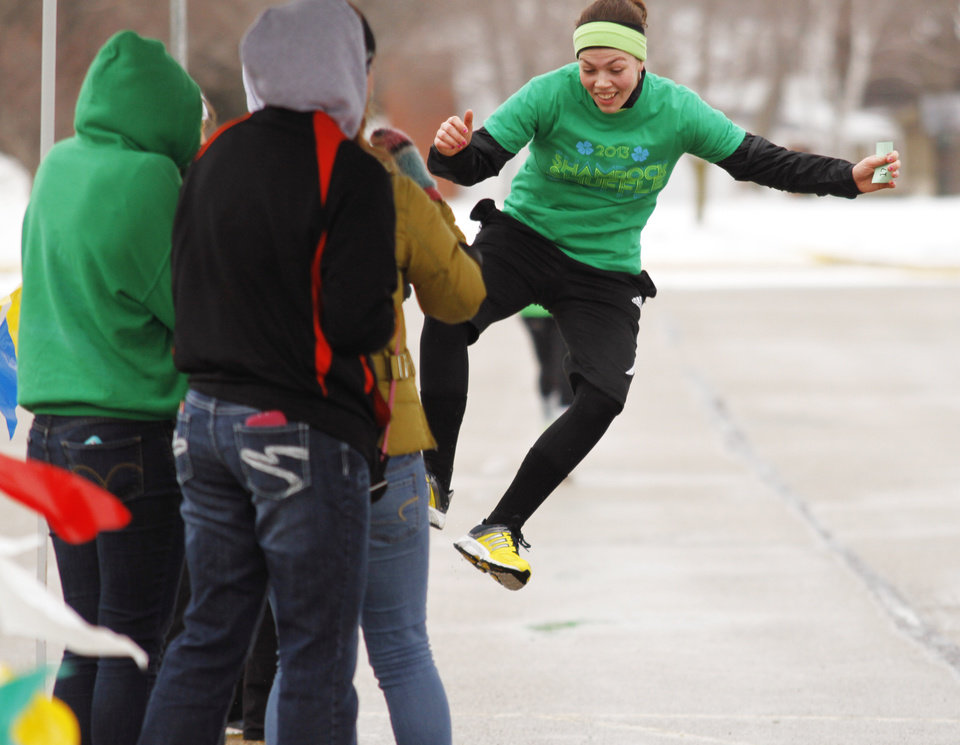 Photo - Maria Stephans of Hartford click her heels together as she crosses the finish line during the Shamrock Shuffle 5K Race/Walk in Hartford on Saturday, March 16, 2013. Proceeds from the race benefited the Hartford Union Varsity Club.  (AP Photo/The Daily News, John Ehlke)