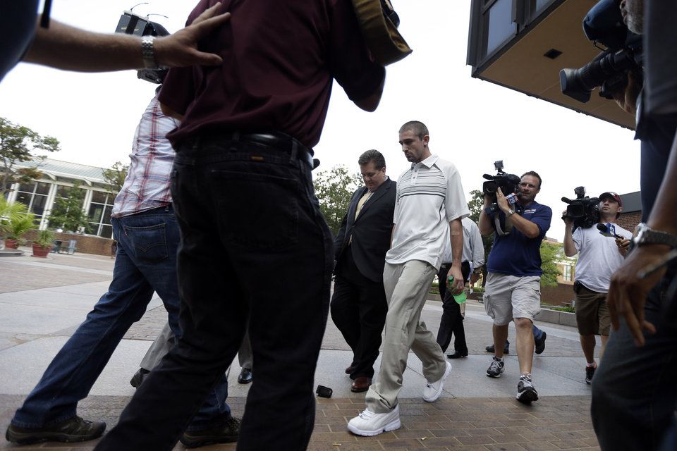 Photo -   Kenneth W. Smith Jr., center, accompanied by his lawyer Bill Brennan, center left, walks near the U.S. Courthouse, Friday, Sept. 7, 2012, in Philadelphia. Smith was arrested and is charged with making a hoax threat that led authorities to recall a plane in midair to the Philadelphia airport. Federal authorities charged 26-year-old Smith Jr. with conveying false and misleading information. According to a criminal complaint, Smith called police at the airport on Thursday, Sept. 6, 2012 and falsely reported a passenger was carrying an explosive substance. Authorities then recalled a Dallas-bound US Airways flight to Philadelphia. (AP Photo/Matt Rourke)