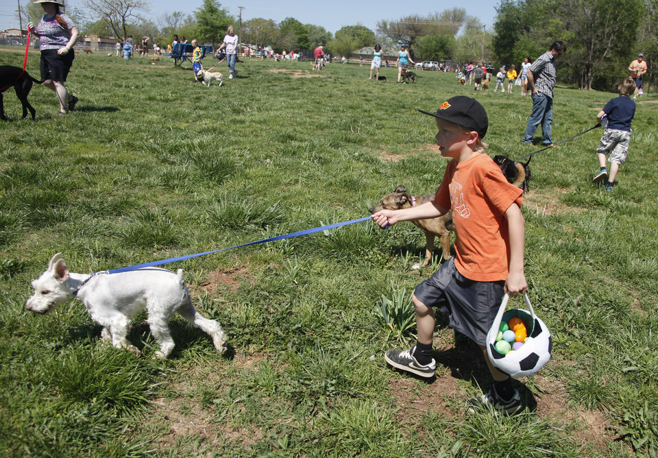 Photo - Lawson Ford, 7, and his dog Oliver, a schnauzer, during the first Hound Hunt, an Easter Egg hunt for dogs inside the dog park at Bick ham-Rudkin Park in Edmond Sunday April 1, 2012. The eggs are filled with dog treats. Photo by Doug Hoke, The Oklahoman