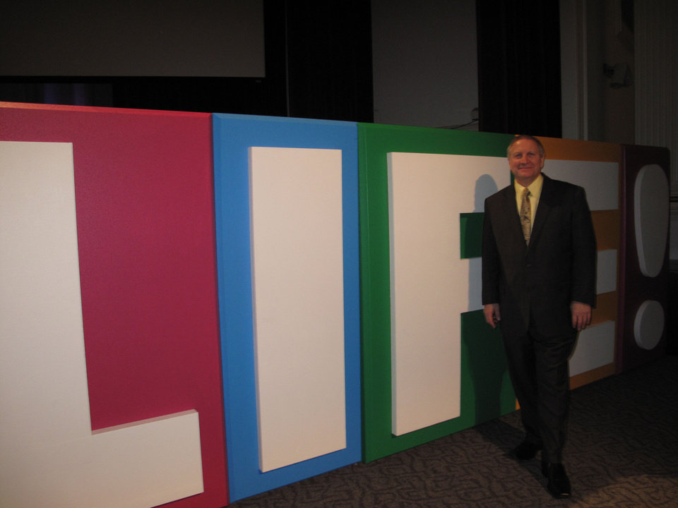 "The Rev. Terry Bates, senior pastor of Faith Church, 800 S Portland, stands next to a colorful display based on his Easter sermon series called ""Life."" Photo by Carla Hinton <strong></strong>"