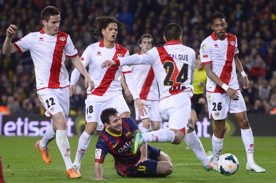 Photo - FC Barcelona's Lionel Messi, from Argentina, third left, duels for the ball against Rayo Vallecano's Iago Falque during a Spanish La Liga soccer match at the Camp Nou stadium in Barcelona, Spain, Saturday, Feb. 15, 2014. (AP Photo/Manu Fernandez)
