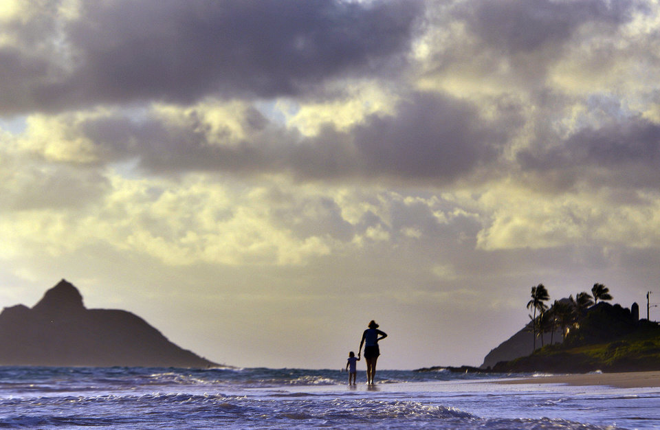 Photo - Anne Kllingshirn of Kailua, Hawaii walks with her daughter Emma, 1, as storm clouds are are seen during the sunrise hours on Kailua Beach, in Kailua, Hawaii, Thursday morning Aug. 7, 2014 . Hurricane Iselle is expected to arrive on the Big Island on Thursday evening, bringing heavy rains, winds gusting up to 85 mph and flooding in some areas. Weather officials changed their outlook on the system Wednesday after seeing it get a little stronger, giving it enough oomph to stay a hurricane as it reaches landfall. (AP Photo/Luci Pemoni)