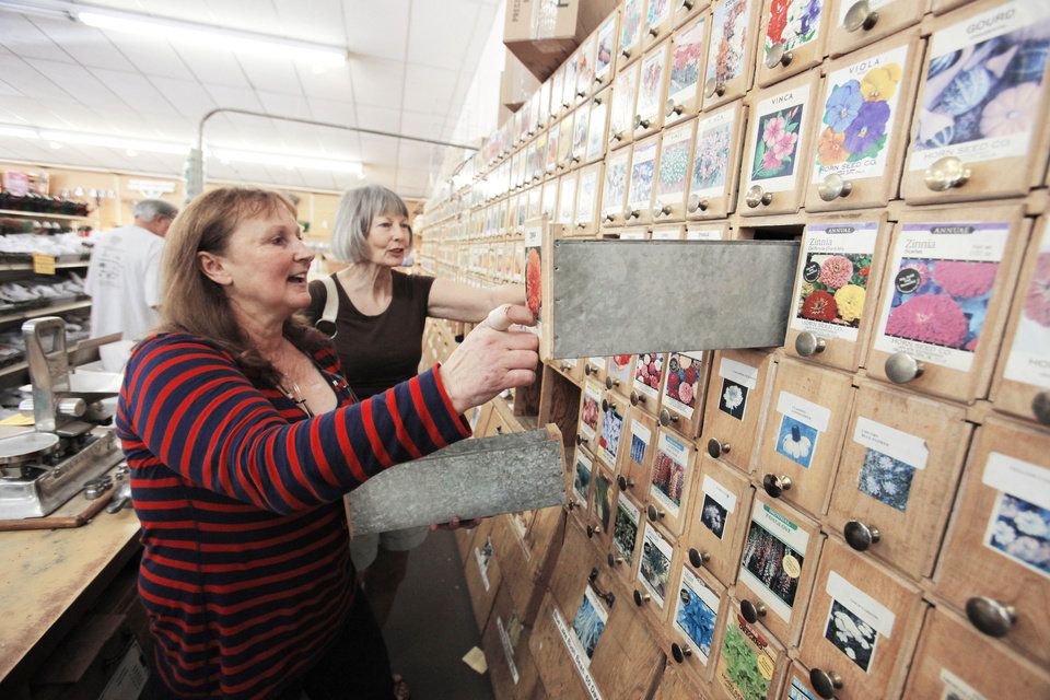 Photo - Horn Seed Co. owner Beverly Shumake helps customer JoAnne Vervinck look for flower seeds. The business is closing after 91 years.  Steve Gooch - The Oklahoman
