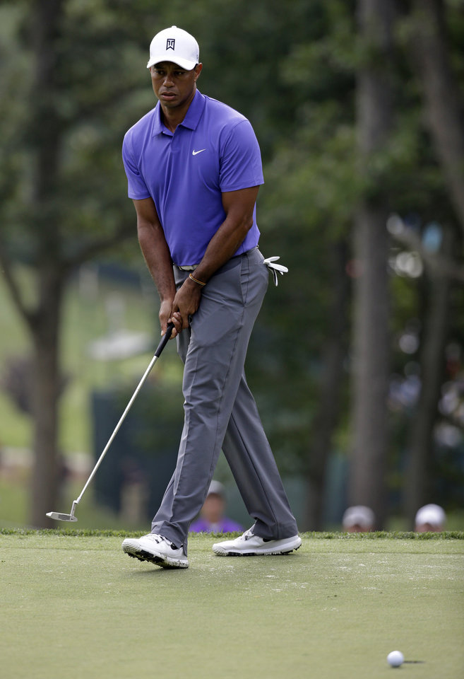 Photo - Tiger Woods reacts to his putt on the 11th hole during the first round of the PGA Championship golf tournament at Valhalla Golf Club on Thursday, Aug. 7, 2014, in Louisville, Ky. (AP Photo/John Locher)