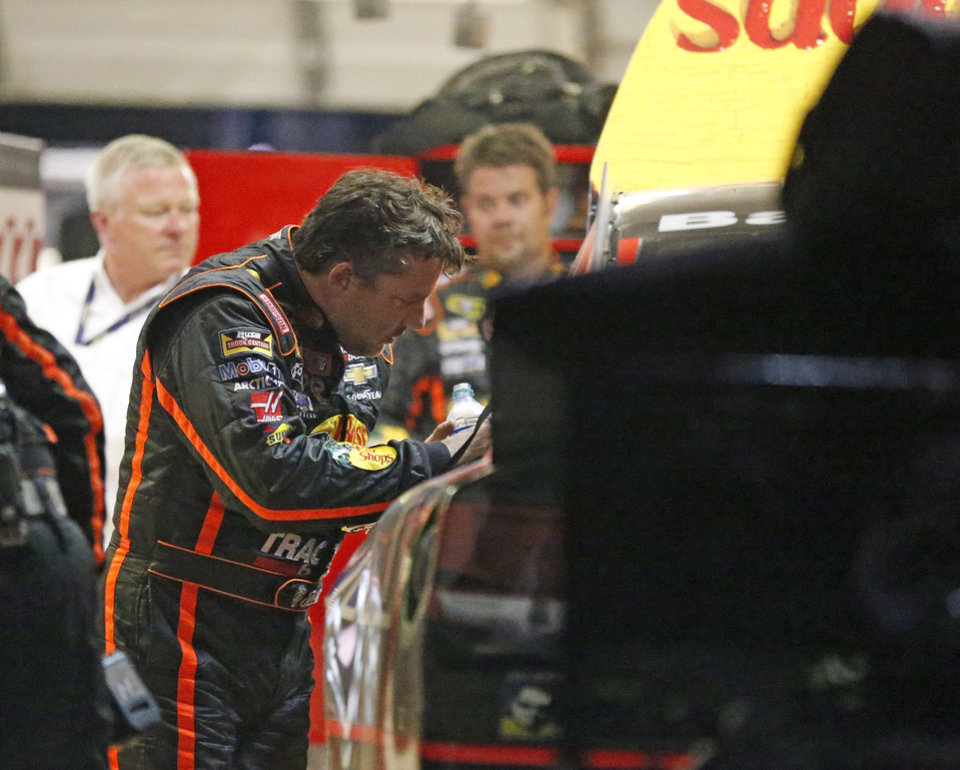 Photo - Sprint Cup Series driver Tony Stewart (14) looks over the damage to his car after he hit the wall during a NASCAR Sprint Cup auto race at Atlanta Motor Speedway Sunday, Aug. 31, 2014, in Hampton, Ga..  (AP Photo/Brynn Anderson)