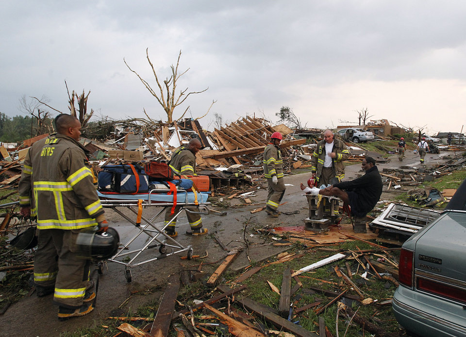 "Birmingham Rescue attends to a man who was injured after a tornado hits Pratt City just north of downtown Birmingham on Wednesday, April 27, 2011, in Birmingham, Ala.  The widespread destruction caused Gov. Robert Bentley to declare a state of emergency by midday, saying tornadoes, severe thunderstorms, hail, and straight-line winds caused damage to ""numerous homes and businesses"" in Alabama. (AP Photo/Butch Dill)"