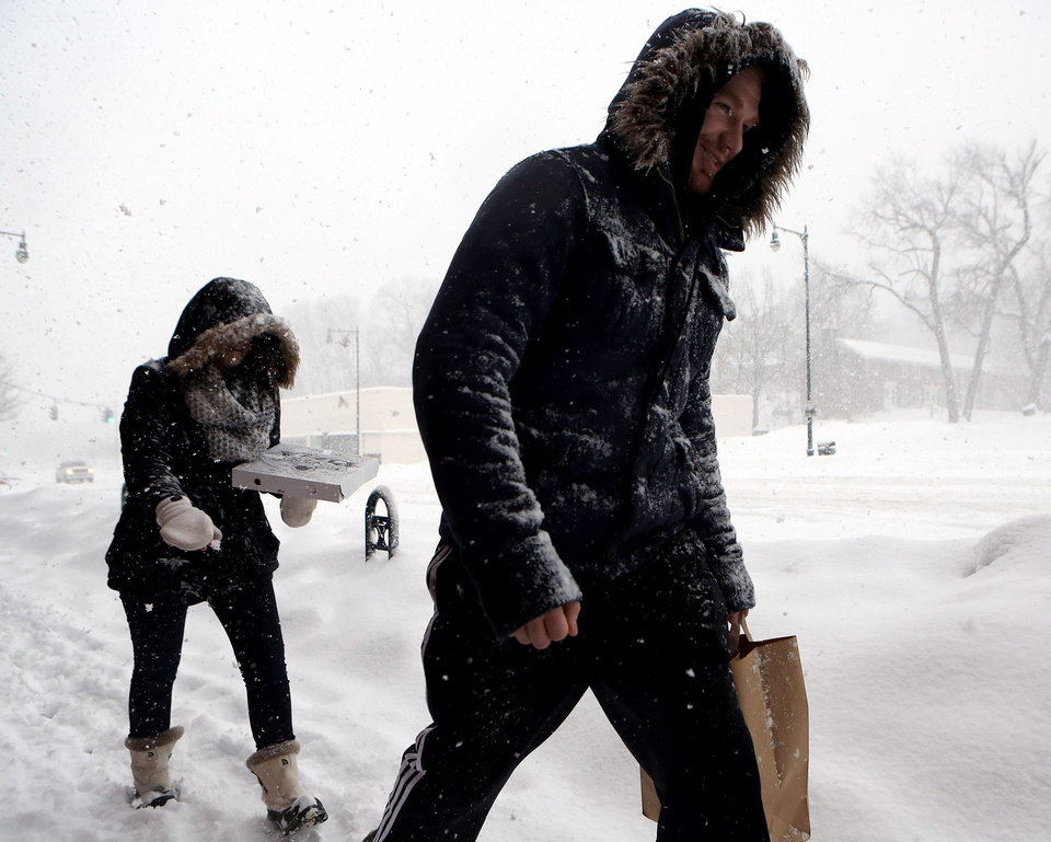 Photo - Alison Brazel, left, and Kyle Bell both of Manchester Conn. brave the snow for pizza and provisions as they walk along Main Street in Manchester on Thursday Feb. 13, 2014. A slow moving winter storm is dumping up to 20 inches of snow and freezing rain across the state, canceling school and making for a messy commute. (AP Photo/Journal Inquirer, Jared Ramsdell) MANDATORY CREDIT