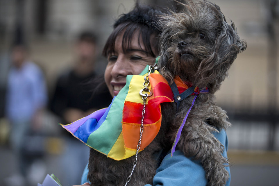 A woman holds a dog wearing a rainbow colored bandana before Argentina's annual gay pride parade in Buenos Aires, Argentina, Saturday, Nov. 10, 2012. Argentina has improved rights for sexual minorities over the last years, becoming the first country in Latin America to legalize same-sex marriage, and this year, the Congress approved Argentina\'s gender identity law, granting people the right to change their legal and physical gender identity simply because they want to, without having to undergo judicial, psychiatric and medical procedures beforehand. (AP Photo/Natacha Pisarenko)