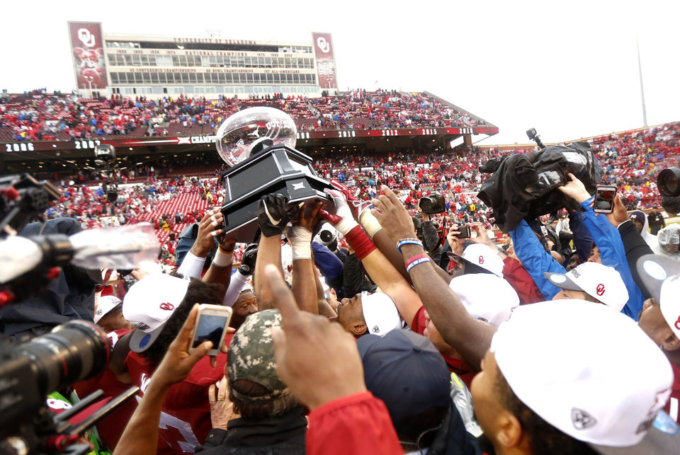 Photo - Oklahoma celebrates with the Big 12 Championship Trophy following the Bedlam college football game between the Oklahoma Sooners (OU) and the Oklahoma State Cowboys (OSU) at Gaylord Family - Oklahoma Memorial Stadium in Norman, Okla., Saturday, Dec. 3, 2016. OU won 38-20. Photo by Sarah Phipps, The Oklahoman
