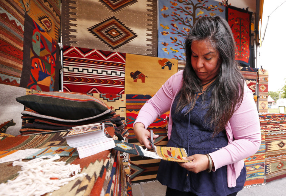 Photo -  Lucy Mendez puts out hand-loomed rugs during the Festival of the Arts.[PHOTO BY STEVE SISNEY, THE OKLAHOMAN]