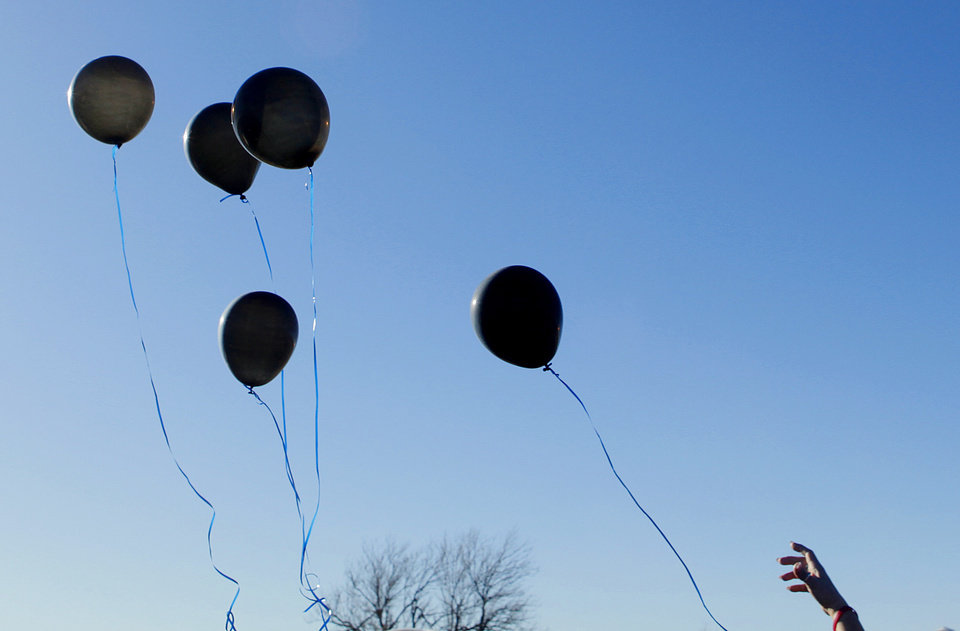 A family member releases five black balloons during in memory of Summer Rust and her four children Kirsten Rust, Autumn Rust, Teagin Rust and Evynn Garas after graveside services  in El Reno, Okla. on Wednesday, Jan. 21, 2009. Rust and her children were killed earlier this month in their apartment in El Reno, Okla.