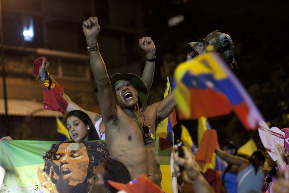 Supporters of Venezuela's President Hugo Chavez celebrate at the Miraflores presidential palace late Sunday Oct. 7, 2012. Venezuela's electoral council said late Sunday President Hugo Chavez has won re-election, defeating challenger Henrique Capriles. (AP Photo/Ramon Espinosa)