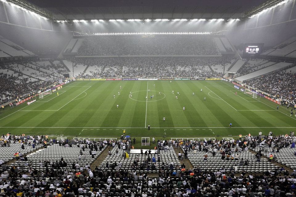 Corinthians\'s and Figueirense players battle it out during a Brazilian soccer league match at the Itaquerao, the still unfinished stadium that will host the World Cup opener match between Brazil and Croatia on June 12, in Sao Paulo, Brazil, Sunday, May 18, 2014. Only 40,000 tickets were put on sale for Corinthians\' match against Figueirense because some of the 20,000 temporary seats needed for the World Cup opener are still being installed. (AP Photo/Andre Penner)