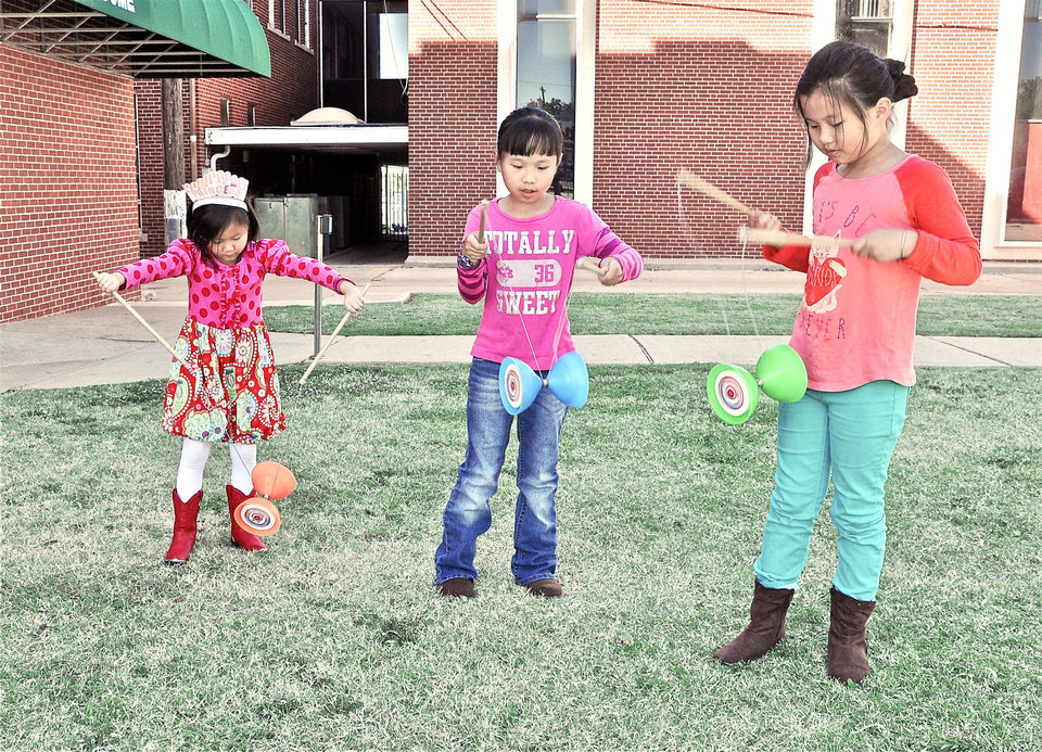 Photo - Birthday girl Abbey Carmichael, 8, of Guthrie, along with cousins Crystal Zhang, and Vicky Zhang, both 8 years old, of Oklahoma City practice their yo yo skills during Chinese culture classes at Trinity International Baptist Church Sunday, October 6, 2013. Photo by M. Tim Blake, for The Oklahoman