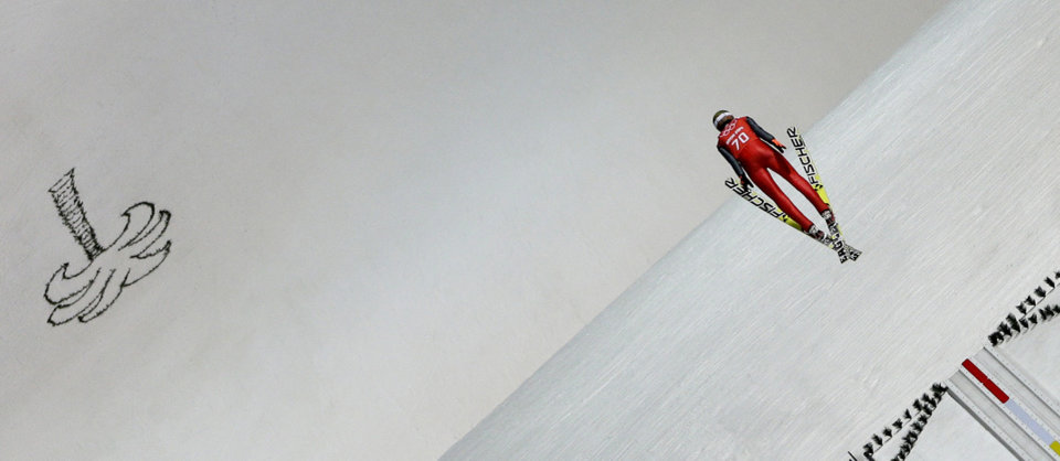 Photo - Poland's Kamil Stoch soars through the air during a men's ski jumping large hill training session at the 2014 Winter Olympics, Wednesday, Feb. 12, 2014, in Krasnaya Polyana, Russia. (AP Photo/Matthias Schrader)