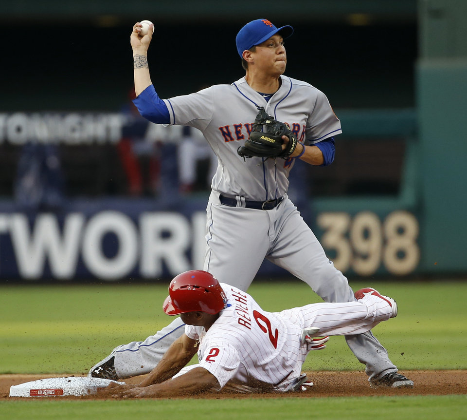 Photo - New York Mets shortstop Wilmer Flores, top, throws to first base after forcing out Philadelphia Phillies' Ben Revere at second on a fielder's choice by Jimmy Rollins during the first inning of a baseball game, Friday, Aug. 8, 2014, in Philadelphia. Rollins was safe at first on the play. (AP Photo/Matt Slocum)