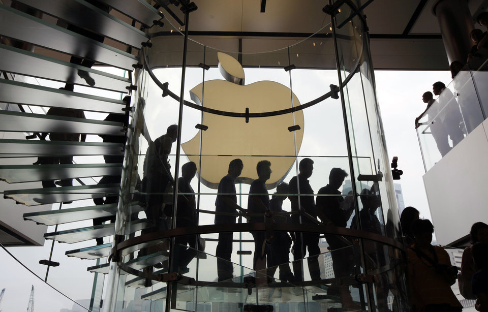 Photo - FILE - In this Sept. 24, 2011, file photo, customers walk past a huge Apple logo at the new store which is located on two floors linked by a glass spiral staircase in Hong Kong's upscale International Financial Center Mall. Friday, January 24, 2014, marks thirty years after the first Mac computer was introduced, sparking a revolution in computing and in publishing as people began creating fancy newsletters, brochures and other publications from their desktops. (AP Photo/Kin Cheung)