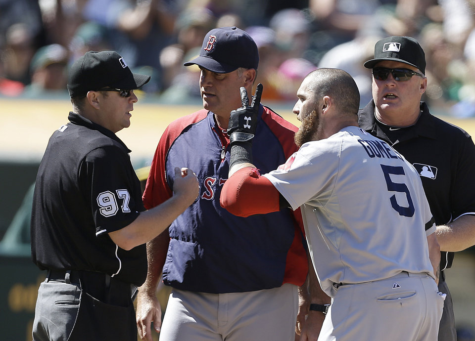 Photo - Boston Red Sox manager John Farrell, second from left, and Boston's Jonny Gomes (5) argue with home plate umpire Todd Tichenor, left, in the ninth inning of a baseball game against the Oakland Athletics on Sunday, July 14, 2013, in Oakland, Calif. (AP Photo/Ben Margot)