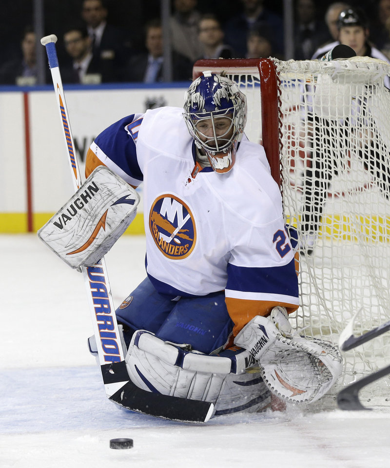 Photo - New York Islanders goalie Evgeni Nabokov defends the net during the second period of the NHL hockey game against the New York Rangers in New York, Thursday, Feb. 7, 2013.  (AP Photo/Seth Wenig)