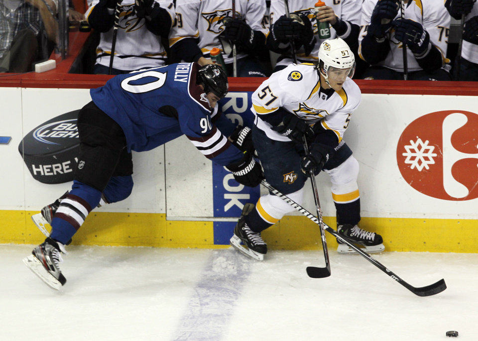 Nashville Predators left wing Gabriel Bourque, right, looks to pass the puck as Colorado Avalanche center Ryan O'Reilly tumbles on the ice in the first period of an NHL hockey game in Denver, Saturday, March 30, 2013. (AP Photo/David Zalubowski)