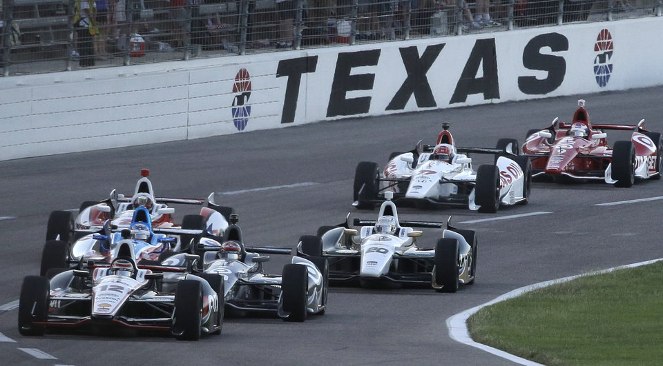 Photo - Pole-sitter Will Power (12) leads the pack at the start of the IndyCar auto race at Texas Motor Speedway in Fort Worth, Texas, Saturday, June 7, 2014. (AP Photo/Tim Sharp)