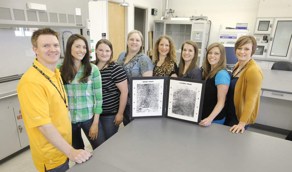 Photo -  Chris Davis, Stormy Gribble, Stacy Fox, Shana Wilson, Meghan Jones, Stacy Hirschman, Amy Stilwell and Amanda Gilson, are members of the OSBI Latent Evidence Unit in their lab at the Forensic Science Center in Edmond. Photo by Paul B. Southerland, The Oklahoman   PAUL B. SOUTHERLAND -  PAUL B. SOUTHERLAND