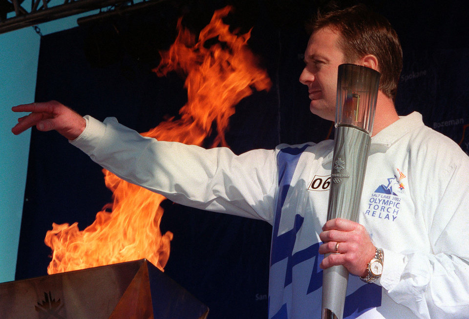 Photo - TORCH RUN, OU: Oklahoma college football coach Bob Stoops acknowledges the crowd after lighting the Olympic cauldron Friday, Jan. 11, 2002, during the Olympic torch relay in Oklahoma City. After a brief presentation, the Olympic flame was carried throughout the city led by Norman, Okla., residents Nadia Comaneci and Bart Conner on its way to Salt Lake City for the Winter Olympics. (AP Photo/Andrew Laker)