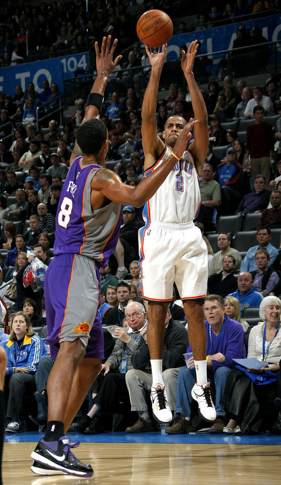 Photo - Oklahoma City's Thabo Sefolosha (2) shoots over Phoenix's Channing Frye during the NBA basketball game between the Oklahoma City Thunder and the Phoenix Suns, Sunday, Dec. 19, 2010, at the Oklahoma City Arena. Photo by Sarah Phipps, The Oklahoman