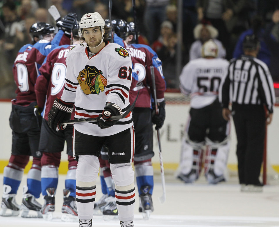 As members of the Colorado Avalanche, back, celebrate a goal by Ryan O\'Reilly, Chicago Blackhawks right wing Michael Frolik (67), of the Czech Republic, skates back to the bench in the second period of an NHL hockey game in Denver, Friday, March 8, 2013. (AP Photo/David Zalubowski)