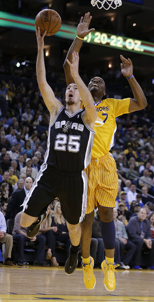 Photo - San Antonio Spurs' Nando De Colo (25) lays up a shot against Golden State Warriors' Carl Landry during the first half of an NBA basketball game Friday, Feb. 22, 2013, in Oakland, Calif. (AP Photo/Ben Margot)