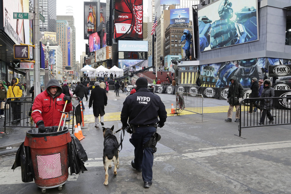Photo - An NYPD officer patrols with a dog, Sunday, Jan. 26, 2014 in New York's Times Square. A dozen blocks of Broadway, in the heart of Manhattan, will close to traffic for four days so the NFL can host a Super Bowl festival. The championship football game between the Denver Broncos and Seattle Seahawks is Sunday, Feb. 3 in East Rutherford, N.J. (AP Photo/Mark Lennihan)