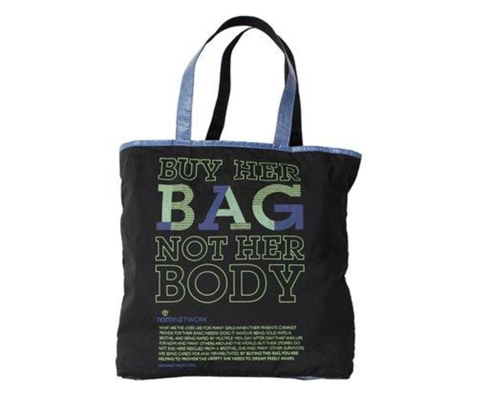 "This undated publicity photo provided by Nomi Network shows a Dark Blue Slogan Zip Tote that has the slogan, ""Buy Her Bag, Not Her Body."" The nonprofit Nomi Network, operating in Cambodia, uses recyclables for colorful, graphic fish feed and rice bags made by women and girls who are victims of human sex trafficking or are vulnerable to falling prey. The company also works with trafficking victims in India. (AP Photo/Nomi Network)"