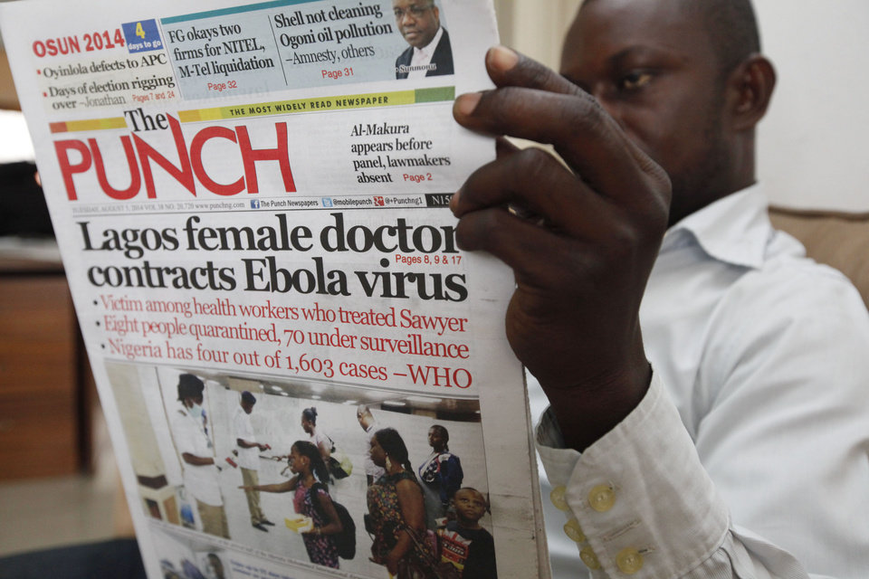 Photo - A man reads a local newspaper with headline news about a Lagos female doctor contracts Ebola Virus, in Lagos, Nigeria, Tuesday, Aug. 5, 2014.  Lagos State Health Commissioner Jide Idris announced Tuesday that eight people are being kept in quarantine with symptoms of Ebola.  (AP Photo/Sunday Alamba)