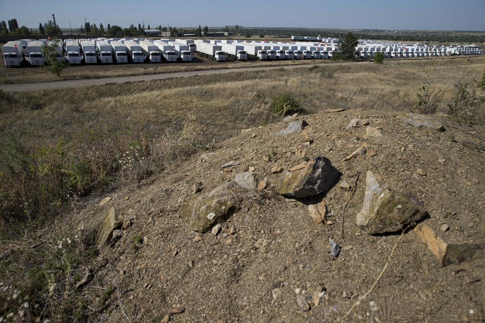 Photo - CORRECTS NAME OF TOWN TO KAMENSK-SHAKHTINSKY. An aid convoy is parked in Kamensk-Shakhtinsky, Russia, Friday, Aug. 15, 2014. The Ukrainian government threatened to use all means available to block the convoy if the Red Cross was not allowed to inspect the cargo. Such an inspection would ease concerns that Russia could use the aid shipment as cover for a military incursion in support of the separatists, who have come under growing pressure from government troops. (AP Photo/Pavel Golovkin)