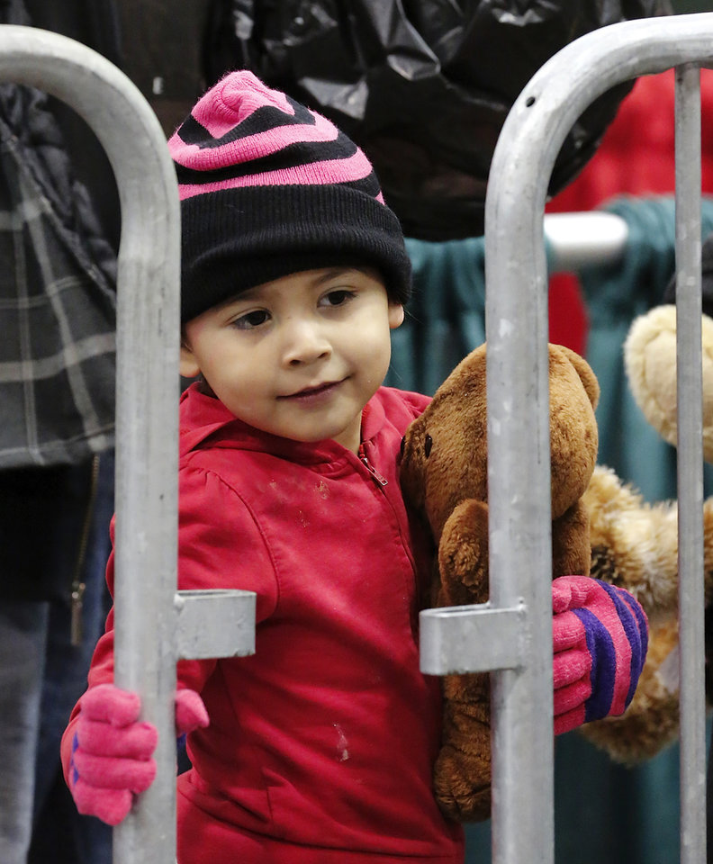 A young boy peeks between the rails of a fence to get a better view of the toys as he waits in the gift line. Hundreds were served a traditional Christmas meal at the annual Red Andrews Dinner inside the Cox Convention Center on Christmas Day, Dec. 25, 2012. An army of volunteers showed up despite snow and ice and hazardous driving conditions. They accompanied each guest through the serving line and carried their trays and seated them at their tables. Other volunteers distributed a small mountain of toys and stuffed animals that were donated for the event. Photo by Jim Beckel, The Oklahoman