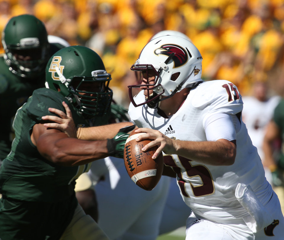 Photo - Louisiana-Monroe quarterback Kolton Browning, right is pressured by Baylor defensive end Terrance Lloyd in the first half of an NCAA college football game, Saturday, Sept. 21, 2013, in Waco, Texas. (AP Photo/Waco Tribune Herald, Rod Aydelotte)