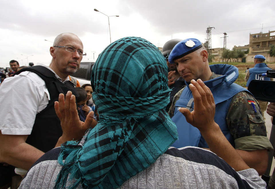 Photo -   In this picture taken during UN observer-organized media tour, a Syrian man, who covers his face to obscure his identity, speaks to UN observers about conditions in Hama city, central Syria, on Thursday May 3, 2012. Syrian security forces stormed dorms at a northwestern university to break up anti-government protests there, killing at least four students and wounding several others with tear gas and live ammunition, activists and opposition groups said Thursday. (AP Photo/Muzaffar Salman)