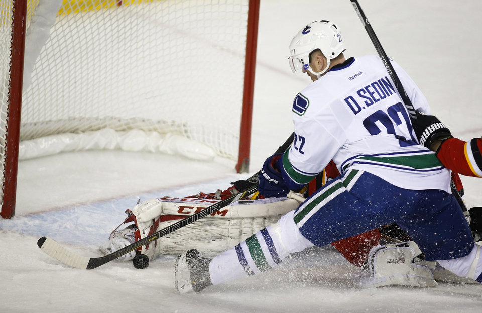 Vancouver Canucks' Daniel Sedin, of Sweden, tries to lift the puck over the pad of Calgary Flames goalie Reto Berra, of Switzerland, while falling to the ice during the second period of an NHL hockey game in Calgary, Alberta, Sunday, Dec. 29, 2013. (AP Photo/The Canadian Press, Jeff McIntosh)