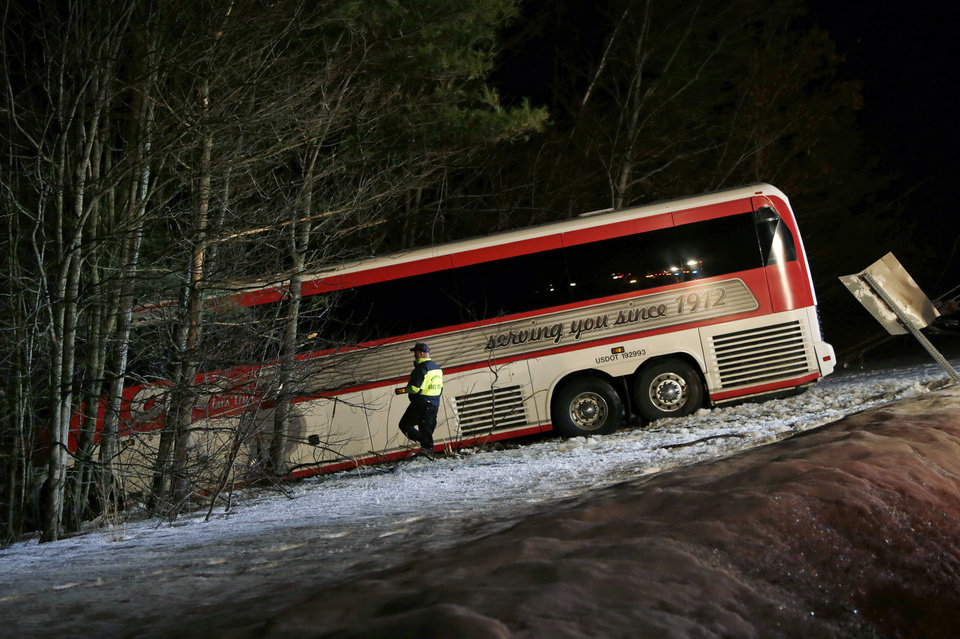 Police work at the scene in Georgetown, Mass. Tuesday, Feb. 26, 2013 where a bus carrying University of Maine basketball players crashed on Route 95, north of Boston, injuring the driver and several students. The driver was seriously injured and was taken by helicopter to a hospital, police said. Twenty-two students were being evaluated or treated for minor injuries, they said. (AP Photo/Elise Amendola)