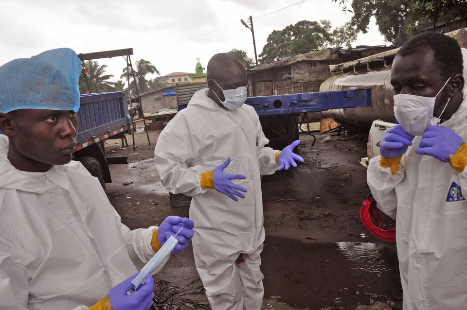 Photo - Liberian health worker prepare their Ebola protective gear before removing the body of a man that they believe died from the Ebola virus  in Monrovia, Liberia, Friday, Aug. 29, 2014.  The Ebola outbreak in West Africa eventually could exceed 20,000 cases, more than six times as many as are now known, the World Health Organization said Thursday. A new plan released by the U.N. health agency to stop Ebola also assumes that the actual number of cases in many hard-hit areas may be two to four times higher than currently reported.(AP Photo/Abbas Dulleh)