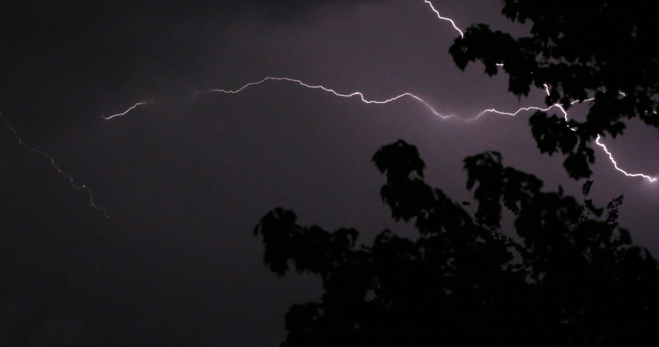 Photo - Lightning crosses the sky above trees in Lawrence, Kan., Thursday, May 8, 2014. The area is under a severe thunderstorm watch. (AP Photo/Orlin Wagner)