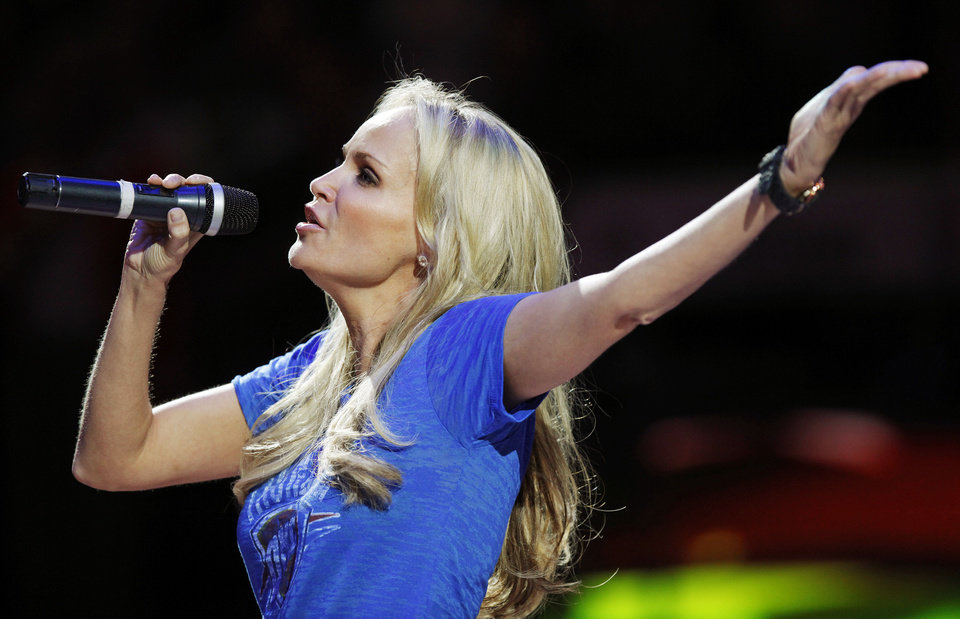 Photo - Kristin Chenoweth sings the national anthem before an NBA basketball game between the Oklahoma City Thunder and the Dallas Mavericks at Chesapeake Energy Arena in Oklahoma City, Thursday, Dec. 29, 2011. Photo by Nate Billings, The Oklahoman